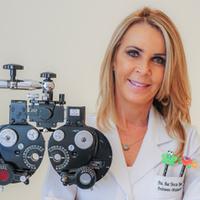 Foto da oftalmologista Ana Tereza. Ela é loira, tem cabelos longos e na foto à frente dela um equipamento oftalmológico.