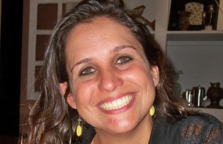 Foto da Jornalista Brisa Teixeira. Ela tem cabelos castanhos e é morena clara