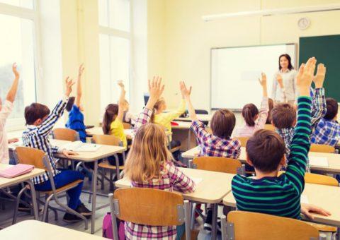 Em uma sala de aula, alunos sentados em suas cadeiras, levantam a mão.