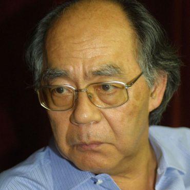 Foto do escritor Içami Tipa. Ele é japonês e usa óculos. É parcialmente calvo e veste camisa azul.