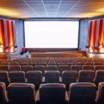 Foto de uma sala de cinema com a tela branca e poltronas vazias.