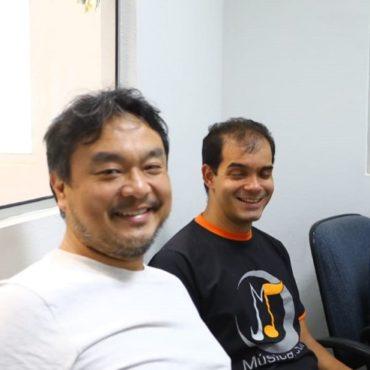 João Egashira,diretor da fase MBP da Oficina de Música de Curitiba e o professor Luiz Amorim, sentados em cadeiras. Sorriem.