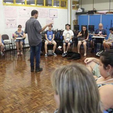 Oficina - Em uma sala aula, alunos em semi-círculo sentados em cadeiras de frente para o professor Luiz Amorim. Professor está em pé de costas para a foto e de frente para os alunos.