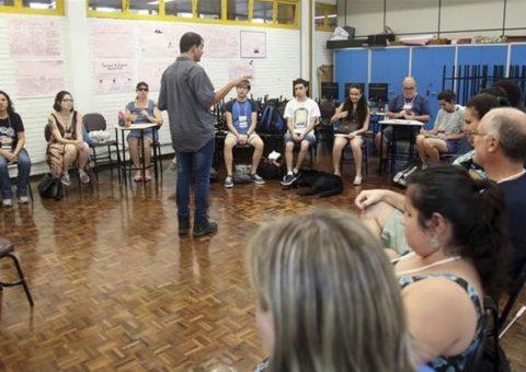 Em uma sala aula, alunos em semi-círculo sentados em cadeiras de frente para o professor Luiz Amorim. Professor está em pé de costas para a foto e de frente para os alunos.