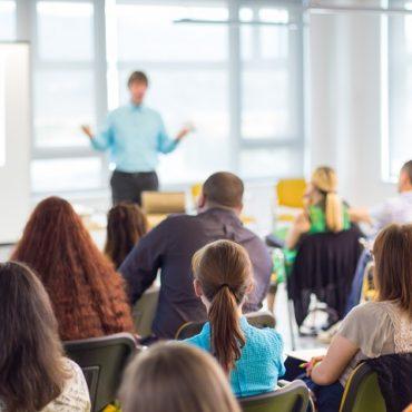 Fotografia colorida de uma sala de aula repleta de alunos e o professor. Os alunos, em primeiro plano, estão sentados de costas para a foto e de frente para o professor. O professor, em imagem desfocada, está de frente para os alunos com os braços flexionados e as mãos viradas para cima. Veste camisa azul e calça preta.