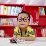 Fotografia colorida de um menino oriental deitado de bruços com os bracinhos flexionados sobre um livro aberto e sob um tapete branco. Ele olha para frente, usa óculos redondos e veste uma camiseta amarela com detalhes riscados em cinza e preto. Está em uma sala como uma estante vermelha repleta de livros atrás dele.