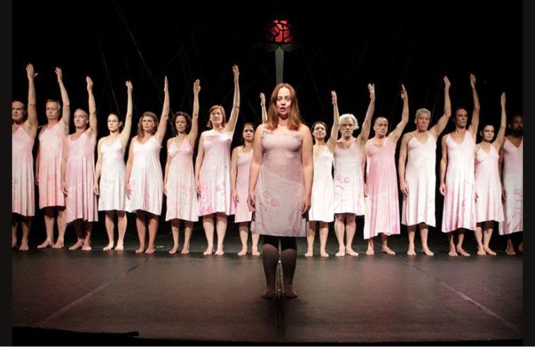 Foto colorida em fundo preto. Atrás um do lado do outro, homens e mulheres vestem camisola branca e estão descalços. Todos sérios e o braço direito estendido para cima. À frente, uma mulher de camisola branca e com os braços estendidos para baixo.
