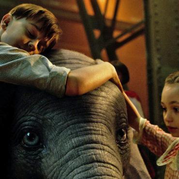 Dumbo ao centro é abraçado por menino e menina. Cena do filme Dumbo com Audiodescrição e Libras.