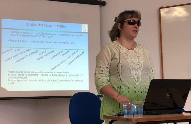 Luciane Molina está em pé. Atrás dela, um telão com um dos slides da sua defesa de mestrado sobre Trajetórias de Estudantes Cegos e as Práticas Escolares Inclusivas. Na frente dela um notebook.