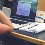 Curso de inclusão Senac: Foto de uma mesa de estudos com computador, caderno e caderno e caneta. Com uma pessoa estudando, em que aprece apenas o braço dela.