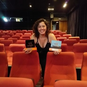 Audiodescritora Andréia Paiva na sala de cinema com estofados vermelho. Ela segura dois troféus do V Festival VerOuvindo