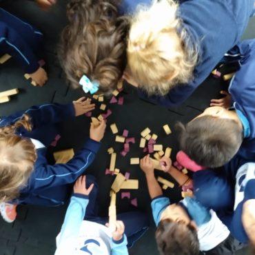 educação: crianças dispostas em círculo brincam com peças de madeira. Foto tirada de cima.