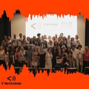 Numa sala de cinema, um grupo de 43 pessoas posa sorridente. Ao fundo, na telona, a marca do V VerOuvindo. Abaixo, à esquerda, sobre fundo laranja com bordas pontiagudas, a marca do VerOuvindo em preto. Audiodescrição, Legendagem e Libras