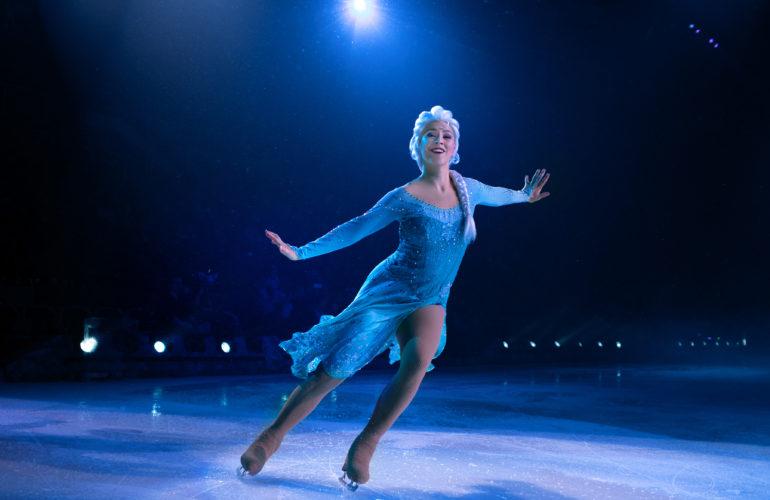 Audiodescrição: Elza patina sorridente de de braços abertos. Seu vestido é azul de mangas compridas. Narração da Audiodescriçãopor Raquel Carissimi