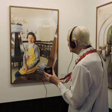 Idosa com fone de ouvido de audiodescrição está de costas e em frente a uma das fotos da exposição Observador, em que aparece uma mulher oriental posando para a foto.