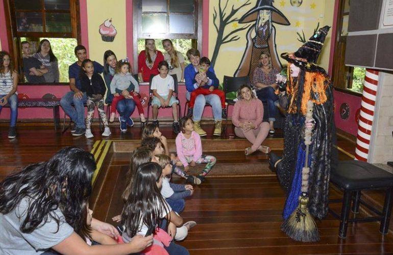 Contação de história inclusiva, na foto, crianças e alguns adultos sentados, alguns no chão, alguns em cadeiras, à esquerda. À direita, a bruxa em pé, com uma vassoura na mão, contando a história. Ao fundo, na parede, a figura de uma bruxa com uma árvore seca a seu lado.