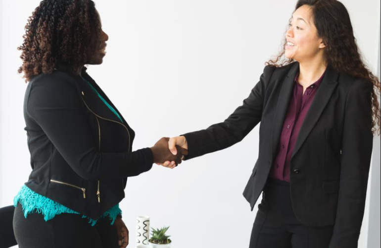 Audiodescrição da foto sobre lei de cotas: duas mulheres estão em pé e apertam as mãos.