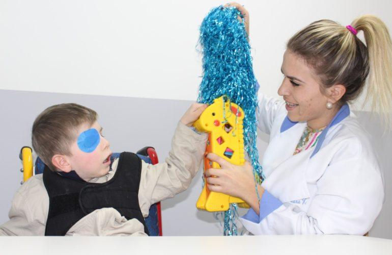 Adaptação escolar - Foto de menino com tampão no olho direito tateia objetos coloridos estimulado por uma professora. Ela sorri.