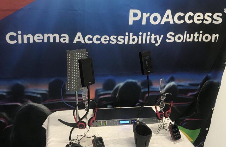 Expocine - Imagem de uma sala de cinema com os equipamentos da Riole acessíveis para pessoas com deficiência visual e auditiva