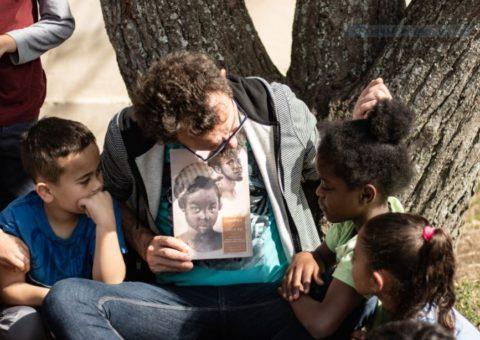 Um homem sentado conta história ao ar livre. Três crianças estão ao redor dele.