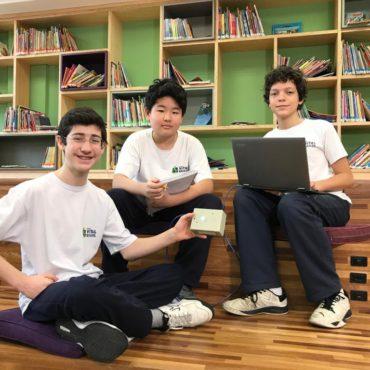 Três alunos sentados no chão de uma Biblioteca. Seguram notebook e um tablet.