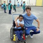 Prática inclusiva Foto quadrada do menino na cadeira de rodas e o professor ao lado agachado e abraçado ao aluno.