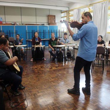 Foto do professor Luiz Amorim em uma sala de aula. Ele está de costas, toca violão para os alunos dispostos em semicírculo.