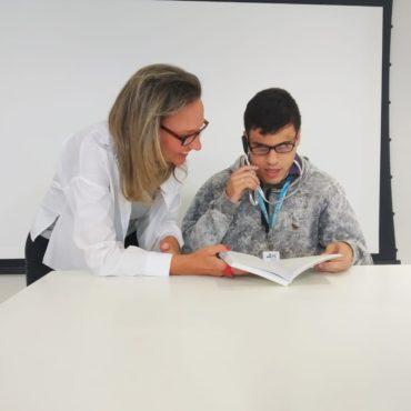 Foto de Michel com o óculos OrCam e um livro nas mãos