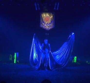 Com uma iluminação na cor azul, uma pessoa em pé com grandes asas.