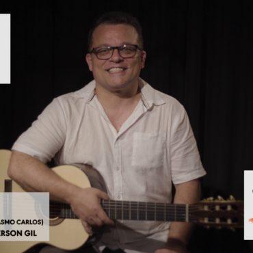 Gil integrante do Curitibôcas segura o violão, sorri para a foto