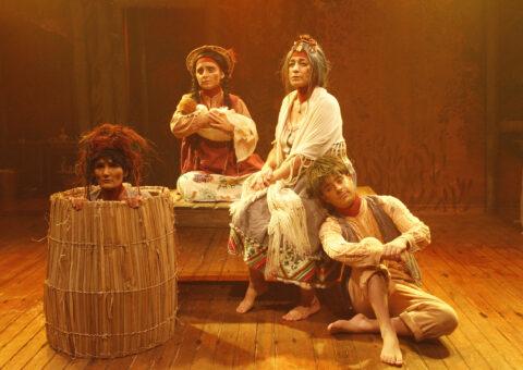 Três mulheres e um homem. Uma dentro de um cesto. A segunda está com um bebê no colo. A terceira é uma senhora. Ela está sentada em um banco. A quarta pessoa é um jovem. Ele está sentado no chão com a cabeça apoiada na senhora.